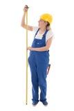 Concetto di carriera - donna in uniforme blu del costruttore che tiene misura t immagini stock
