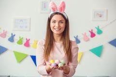 Concetto di celbration di pasqua della giovane donna a casa in orecchie di un coniglietto che giudicano le uova allegre immagine stock libera da diritti