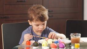 Concetto di celebrazione di Pasqua Ragazzino felice che decora le uova di Pasqua per la festa stock footage