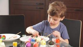 Concetto di celebrazione di Pasqua Ragazzino felice che decora le uova di Pasqua per la festa archivi video