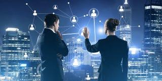 Concetto di collegamento e di rete sociali contro la vista della città di notte e partner che lavorano in collaborazione Immagini Stock