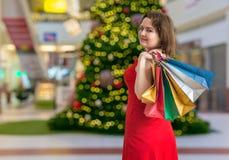 Concetto di compera di Natale La giovane donna graziosa è regali di compera Fotografie Stock Libere da Diritti