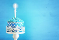 Concetto di compleanno con il bigné ed una candela sulla tavola di legno immagini stock libere da diritti