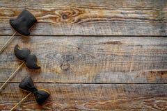 Concetto di compleanno degli uomini Insieme dei biscotti nella forma dello smoking, dei baffi e del cappello Copyspace di legno d Immagini Stock