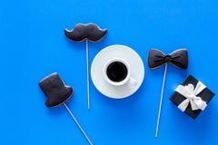 Concetto di compleanno degli uomini Smoking, biscotti del cappello e dei baffi e scatola del goft Vista superiore del fondo blu Fotografia Stock