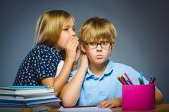 Concetto di comunicazione della scuola ragazza che bisbiglia in orecchio del ragazzo Fotografie Stock Libere da Diritti