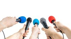 Concetto di conferenza e di giornalismo Molti microfoni della tenuta delle mani del reporter Fotografia Stock