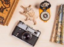 concetto di corsa Bussola, retro photocamera e conchiglia su un backgroun di legno Immagini Stock