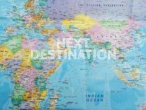 concetto di corsa DESTINAZIONE SEGUENTE della lettera sulla mappa di mondo Immagine Stock Libera da Diritti