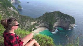 concetto di corsa Donna che si siede sulla scogliera, guardante la spiaggia di Kelingking su Nusa Penida stock footage