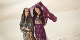 concetto di corsa Due sorelle gordeous delle donne che viaggiano nel deserto Stelle del cinema indiane arabe Immagine Stock