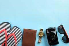 concetto di corsa macchina fotografica, passaporto, Flip-flop e vetri su un fondo blu luminoso Vista superiore fotografia stock