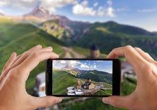 concetto di corsa Mani che rendono foto della chiesa ortodossa di Gergeti alta nelle montagne, Georgia Immagine Stock