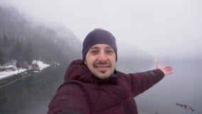 concetto di corsa Uomo che prende selfie e che mostra il lago Ritsa in Abkhazia nell'inverno video d archivio