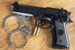 Concetto di crimine con la rivoltella, le manette e le pallottole su un fondo di legno Fotografia Stock