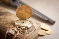 Concetto di crimine e di gioco con le monete e la pistola di oro Fotografia Stock