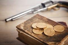 Concetto di crimine e di gioco con le monete e la pistola di oro Immagini Stock