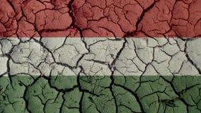 Concetto di crisi: Crepe del fango con la bandiera dell'Ungheria fotografie stock