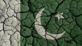 Concetto di crisi: Crepe del fango con la bandiera del Pakistan fotografie stock libere da diritti