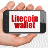 Concetto di Cryptocurrency: Passi la tenuta dello Smartphone con il portafoglio di Litecoin su esposizione Fotografie Stock