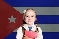 Concetto di Cuba con la studentessa felice del bambino con il libro contro la bandiera di fondo cubano immagini stock libere da diritti