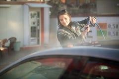 Concetto di cura del trasporto Automobile di lavaggio nel distributore di benzina di auto con l'artificiere ad alta pressione Fotografie Stock Libere da Diritti