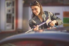 Concetto di cura del trasporto Automobile di lavaggio nel distributore di benzina di auto con l'artificiere ad alta pressione Immagini Stock