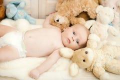 Concetto di curiosità e di infanzia Neonato con i suoi giocattoli molli immagini stock