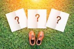 Concetto di decisione con la scarpa di cuoio del giocattolo sulle sedere di struttura del campo di erba Fotografie Stock