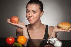 Concetto di dieta: hamburger e mela della tenuta della donna fotografia stock libera da diritti