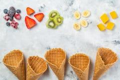 Concetto di dieta sana - frutti e bacche congelate in coni gelati su fondo rustico Fotografie Stock Libere da Diritti
