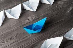 Concetto di direzione di affari con le barche di carta di colore e di bianco sopra Fotografia Stock