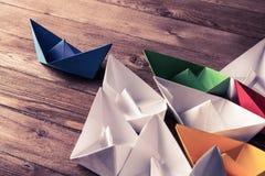 Concetto di direzione di affari con le barche di carta di colore e di bianco sopra Immagini Stock
