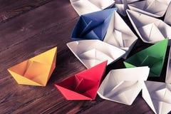 Concetto di direzione di affari con le barche di carta di colore e di bianco sopra Fotografie Stock