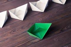 Concetto di direzione di affari con le barche di carta di colore e di bianco sopra Immagine Stock