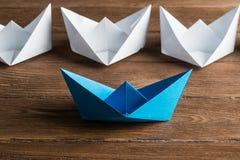 Concetto di direzione di affari con le barche di carta di colore e di bianco sulla tavola di legno Fotografia Stock