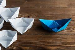 Concetto di direzione di affari con le barche di carta di colore e di bianco sulla tavola di legno Fotografie Stock