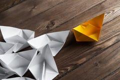 Concetto di direzione di affari con le barche di carta di colore e di bianco sulla tavola di legno Immagini Stock Libere da Diritti