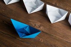 Concetto di direzione di affari con le barche di carta di colore e di bianco sulla tavola di legno Immagini Stock