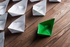 Concetto di direzione di affari con le barche di carta di colore e di bianco sulla tavola di legno Immagine Stock