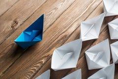 Concetto di direzione di affari con le barche di carta di colore e di bianco sulla tavola di legno Immagine Stock Libera da Diritti