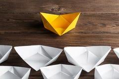 Concetto di direzione di affari con le barche di carta di colore e di bianco sulla tavola di legno Fotografie Stock Libere da Diritti