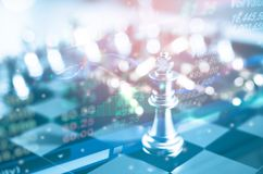 Concetto di direzione di investimento: Il pezzo degli scacchi di re con scacchi altri vicino va giù dal concetto di galleggiament Fotografia Stock