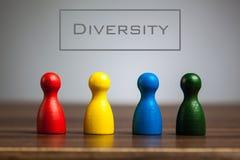 Concetto di diversità con quattro figurine del pegno sulla tavola immagine stock