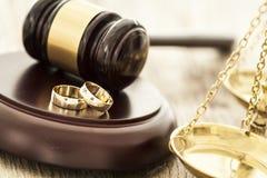 Concetto di divorzio con il martelletto e le fedi nuziali Fotografia Stock