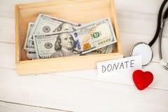 Concetto di donazione Scatola con i dollari su fondo bianco donazioni Di alta risoluzione Fotografie Stock