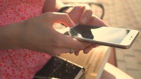 Concetto di e-banking: giovane donna con il telefono online di applicazione della banca al parco stock footage