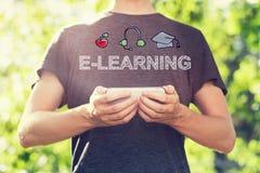 Concetto di e-learning con il giovane che tiene il suo smartphone fuori Immagine Stock