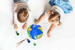 Concetto di ecologia con due bambini prety che dipingono terra su fondo bianco immagine stock