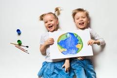 Concetto di ecologia con due bambini prety che dipingono terra su fondo bianco fotografia stock libera da diritti